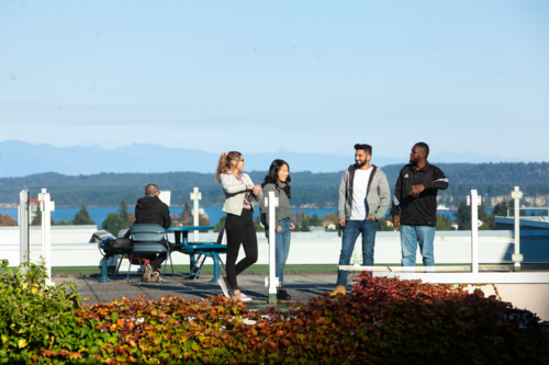 four students talking to each other on a VIU building rooftop