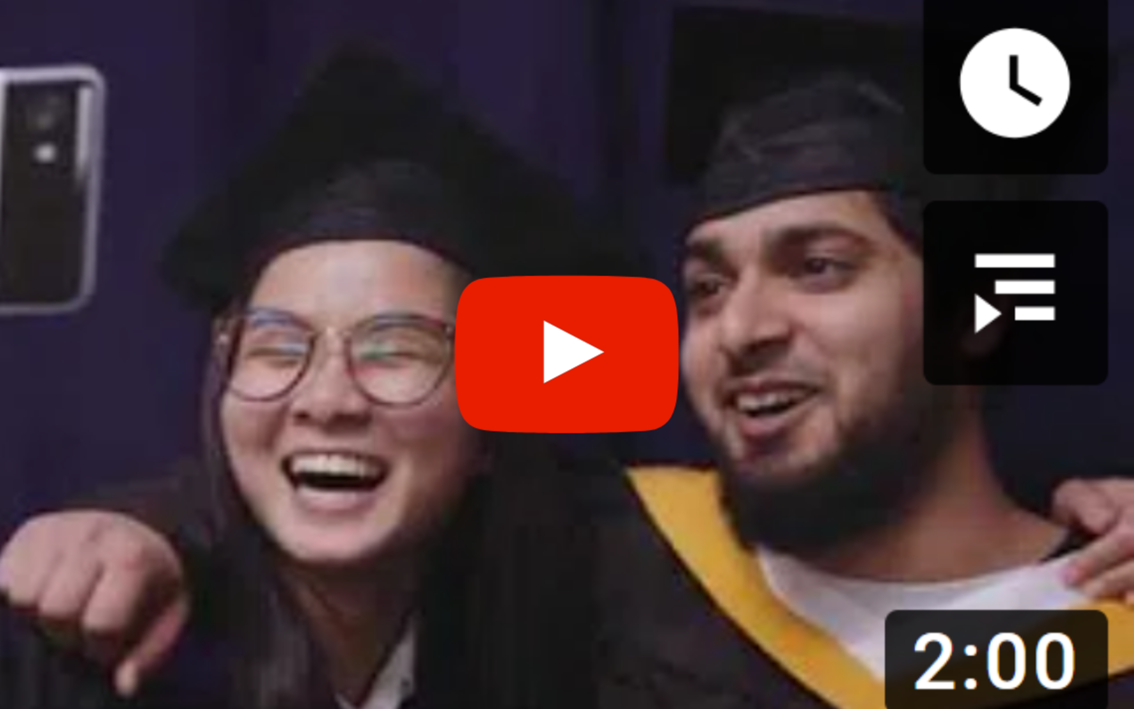 two students smiling each other in the graduation attire